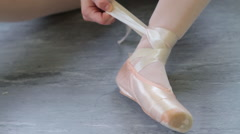 Girl tying ballet shoes, close up Stock Footage