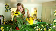 Young woman watering sunflower in small room Stock Footage