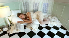Young woman sleeping and waking with feathers falling on her Stock Footage
