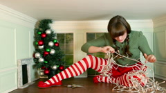 Young woman getting frustrated trying to decorate christmas tree in small room Stock Footage