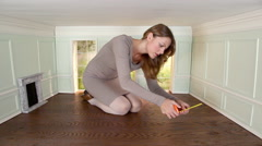 Young woman measuring floor in small room Stock Footage