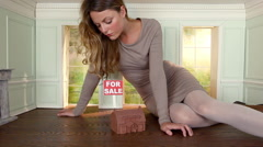 Young woman in small house with model house and for sale sign Stock Footage
