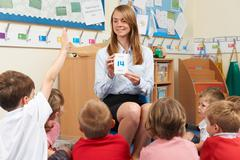Teacher Using Number Flash Cards To Teach Maths - stock photo