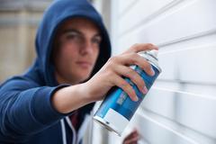 Teenage Boy Spray Painting Garage Door - stock photo