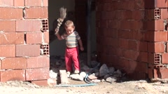 Toddler gets a broom and sweeps mortar sand Stock Footage