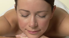 Woman lying on massage table, opening eyes and smiling, zoom out Stock Footage