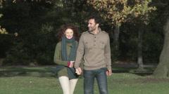 Couple walking through park - stock footage