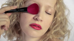Young woman using make up brush on face - stock footage