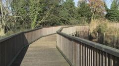 Couple walking across bridge hand in hand Stock Footage