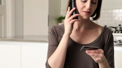Woman on telephone with credit card - stock footage