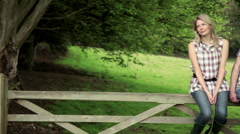 Young couple sitting on gate in countryside Stock Footage