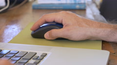 4k dolly shot of a hand clicking and moving a wireless mouse on a laptop - stock footage