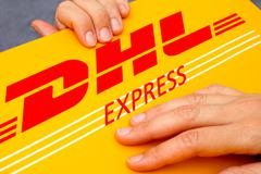 DHL Express package in human hands Stock Photos