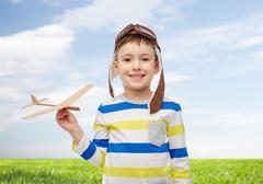 Happy little boy in aviator hat with airplane Stock Photos