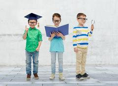 kids in glasses with book, lens and bachelor hat - stock photo