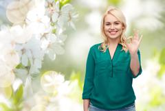 Stock Photo of smiling young woman in shirt showing ok hand sign