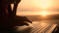 Blogger typing on laptop on beach in slow motion - stock footage
