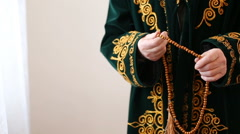An old mullah in national dress praying with rosary beads in hands Stock Footage