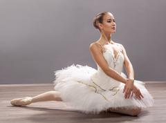 Ballerina is wearing a white tutu and pointe shoes - stock photo
