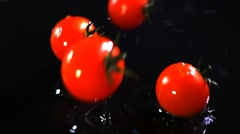 Slow motion of tomatoes falling with water drops on black surface. - stock footage