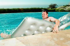 Man falling off lilo - stock photo
