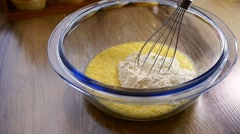 Closeup of mixing flour with already beaten up eggs and sugar using an hand mixe Stock Footage