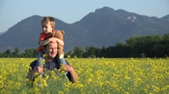 Father giving  a piggy ride to his son in blossom rape field showing farmland  Stock Footage