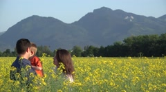 Happy young family in blossom rape field, laughing together Stock Footage
