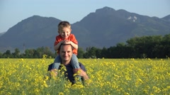 Father giving piggy ride to his laughing baby, together in rape blossom field Stock Footage