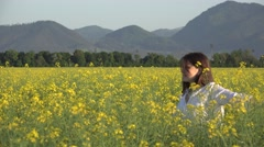 Young woman in rape blossom field enjoy to touch plants - stock footage