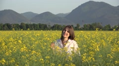 Portrait of beautiful young woman smiling to camera, blossom rape field Stock Footage