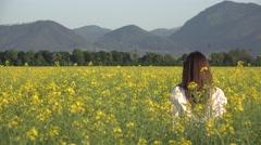 Woman back standing on blossom rape field, enjoy nature - stock footage