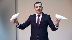 Young attractive showman holding a coupe of the pigeons. Stock Footage