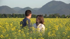 Couple of lovers in blossom rape field, woman playing with a flower - stock footage