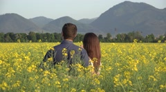 Woman and man standing together in blossom rape field, couple  in nature Stock Footage