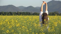 Woman in blossom rape field rising up hands to the sky - stock footage