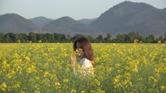 Beautiful young woman portrait, playing with a flower in rape field, pure joy - stock footage