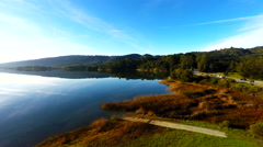 Aerial 4k of serene lakeside with reflective blue sky and road with traffic Stock Footage