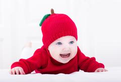 Smiling baby girl playing on her tummy wearing a red apple hat Stock Photos