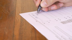 Stock Video Footage of Hand writing numbers on paper tax form with a pen in 4k dolly close up