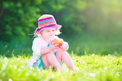 Toddler girl eating an aple in the garden - stock photo