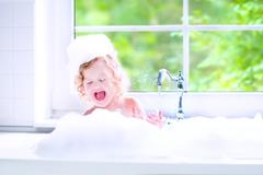 Funny baby girl playing with water and foam in a big kitchen sink Stock Photos