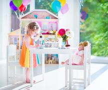 Toddler girl playing tea party with a doll Stock Photos