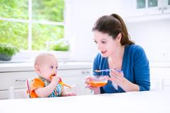 Baby boy eating his first solid food - stock photo