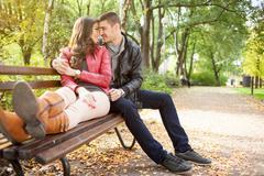 Couple enjoying golden autumn fall season in park Stock Photos