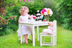 Toddler girl playing tea party with a doll - stock photo