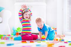 Kids playing with wooden blocks Stock Photos