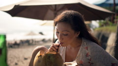 Happy woman relaxing and drinking coconut cocktail in beach bar Stock Footage