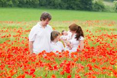Beautiful family of four standing in a gorgeous poppy flower field Stock Photos