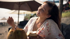 Happy woman drinking cocktail and eating coconut in beach bar Stock Footage
